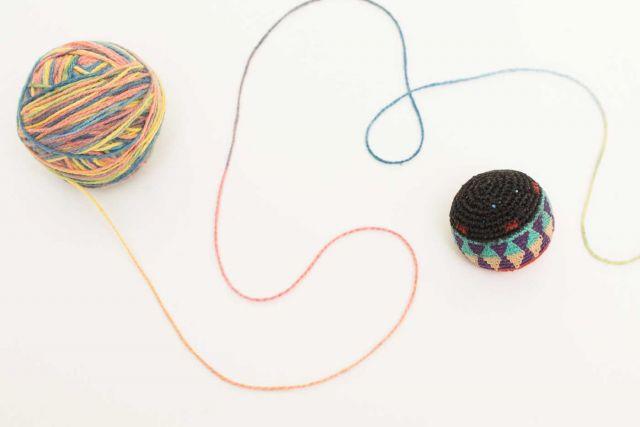 Ein Wollknäuel bunter Wolle und ein Jonglierball